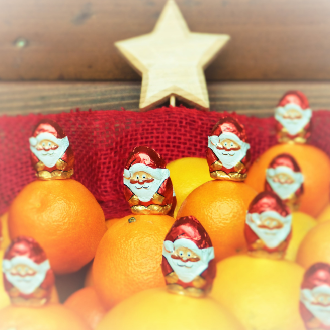 A bowl of chocolate Santas with oranges