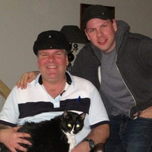 Gary and his dad pose with a cat