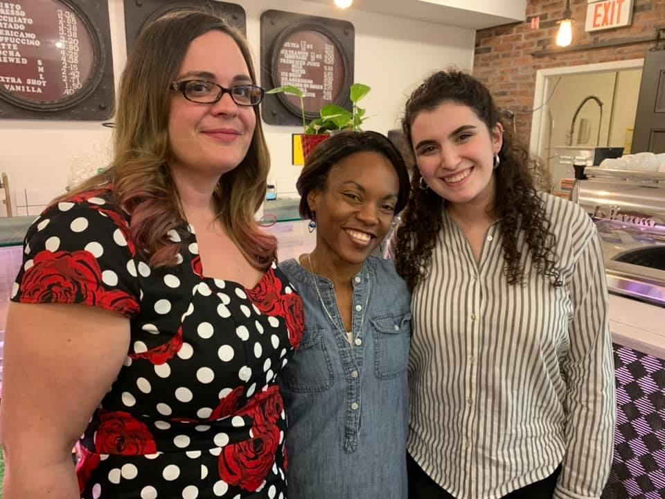 3 women pose in front of coffee counter at 9 bars where community meetings take place